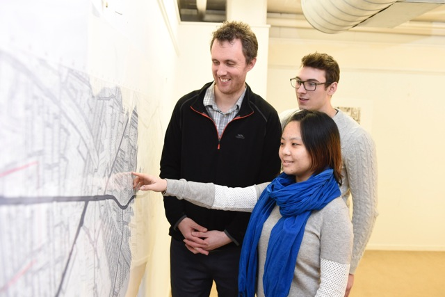 Queen's students Mark Glover and Yijing Wang show their completed map of community resources in the area to Jonny Currie, representing their client, the East Belfast Community Development Agency